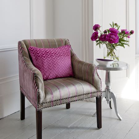 Clarke and Clarke -  Metro Velvets Fabric Collection - A pink, herringbone cushion, and a striped, pink and gold armchair with accompanying silver table and flower arrangement