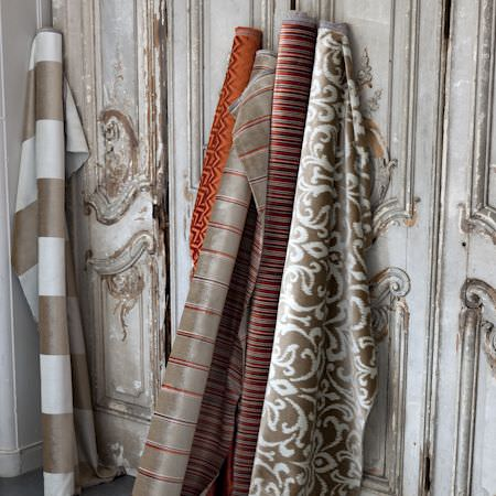 Clarke and Clarke -  Metro Velvets Fabric Collection - Rolls of orange, red, gold and white fabric in a reclaimed, vintage interior