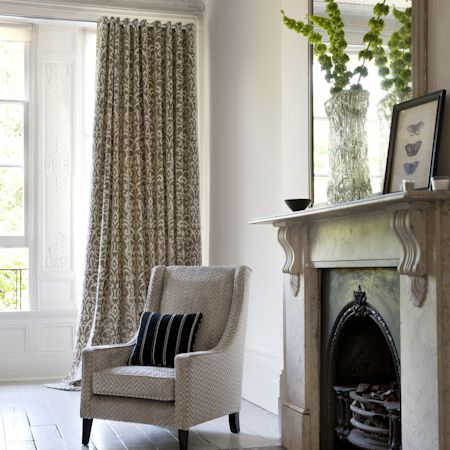 Clarke and Clarke -  Metro Velvets Fabric Collection - A grey, herringbone upholstered armchair with a stripey, black and white cushion by the fireplace and window with white and gold curtains