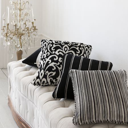 Clarke and Clarke -  Metro Velvets Fabric Collection - White and black striped and patterned cushions of plush, thick fabric on a white, upholstered bench