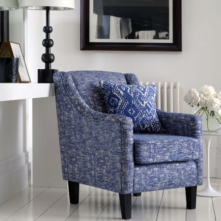Clarke and Clarke -  Mirador Fabric Collection - An armchair covered with patchily coloured blue and white fabric, with a patterned cushion, a round white table and a lamp
