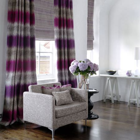 Clarke and Clarke -  Mirador Fabric Collection - A patterned grey and white armchair, horizontally striped purple, violet and grey curtains, a black table and a white bench