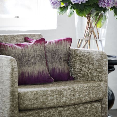 Clarke and Clarke -  Mirador Fabric Collection - Purple, pink, grey and brown fading into each other on two cushions, on an unevenly coloured brown and white armchair