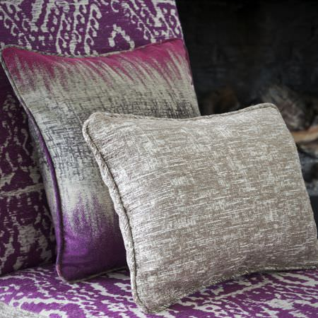 Clarke and Clarke -  Mirador Fabric Collection - A purple and grey tribal print padded chair, with two blurred and patchily coloured purple, pink, white and grey cushions