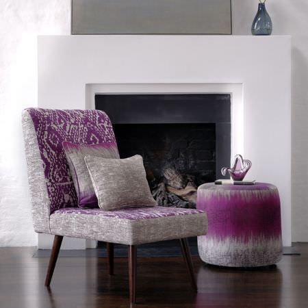 Clarke and Clarke -  Mirador Fabric Collection - Violet and light grey blurred and tribal patterned fabrics covering a chair, a round footstool and two square cushions