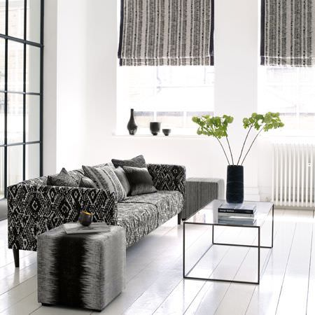 Clarke and Clarke -  Mirador Fabric Collection - Striped blinds, a footstool with blurred colouring, a tribal patterned sofa and assorted cushions, all in black and grey