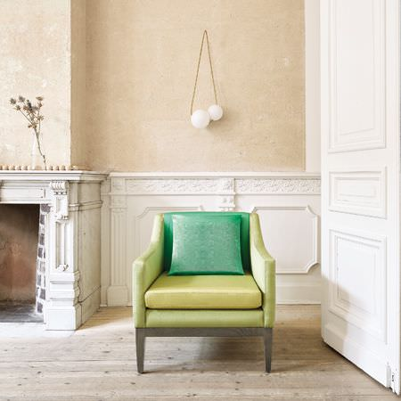 Clarke and Clarke -  Moire Fabric Collection - A simple armchair with apple green sides, a lime green seat, and a back and a cushion in emerald green, with wooden legs