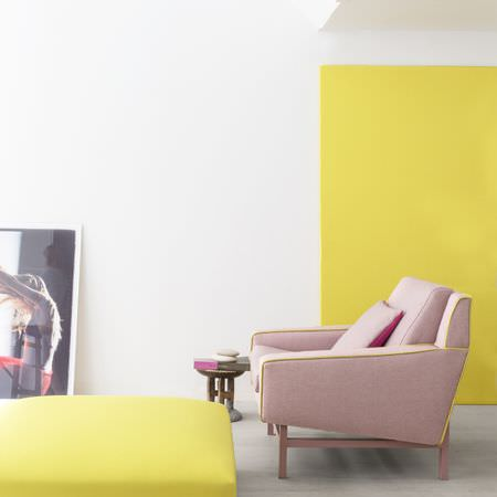 Clarke and Clarke -  Monsoon Fabric Collection - A plain baby pink armchair with a cushion in slightly darker pink, with a square yellow footstool and a small wood table