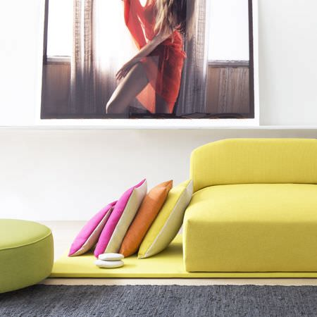 Clarke and Clarke -  Monsoon Fabric Collection - A low, simple, bright yellow sofa with a round apple green footstool and plain pink, orange, yellow and white cushions