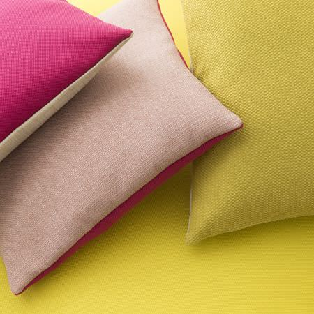 Clarke and Clarke -  Monsoon Fabric Collection - A yellow background behind three plain double-sided cushions; hot pink and white, hot pink and baby pink, yellow and white