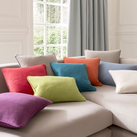 Clarke and Clarke -  Nantucket Fabric Collection - Purple, red, green, blue, orange, mauve, cream and beige scatter cushions on a stone coloured corner sofa