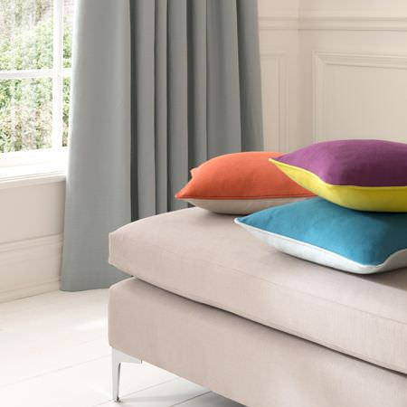 Clarke and Clarke -  Nantucket Fabric Collection - Plain light blue-grey curtains, stone coloured seat, with double sided cushions (purple and green-yellow, orange and beige, blue and white)