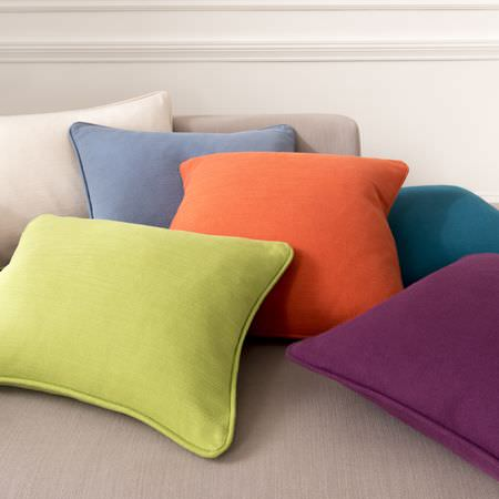 Clarke and Clarke -  Nantucket Fabric Collection - Square scatter cushions in plain green, orange, mauve, blue, purple and cream fabrics, on a stone coloured sofa