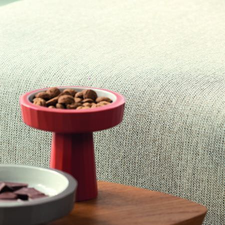 Clarke and Clarke -  Natural Elements Fabric Collection - Red and grey tower-like bowls on a wooden table, beside a large grey fabric seat