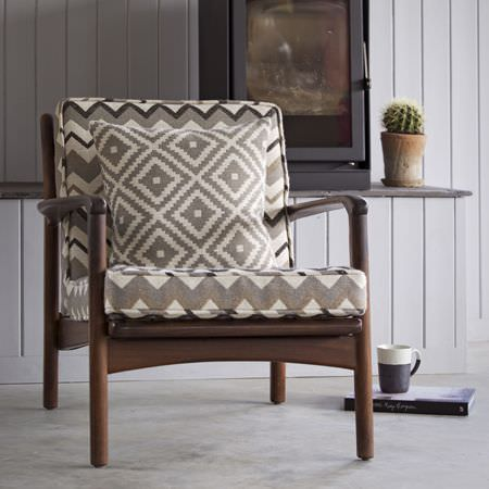 Clarke and Clarke -  Navajo Fabric Collection - A wooden armchair with off-white and grey-beige zigzag print back and seat cushions, with a matching diamond print cushion