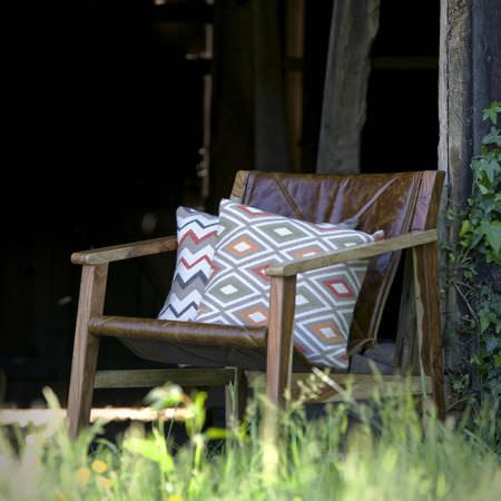 Clarke and Clarke -  Navajo Fabric Collection - A brown leather and wood deck chair style armchair, with two diamond and zigzag cushions in white, grey, red and orange