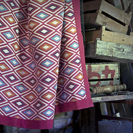 Clarke and Clarke -  Navajo Fabric Collection - Purple, dark pink, sky blue, white and orange diamonds printed on a large throw, edged in fuschia, beside wooden boxes