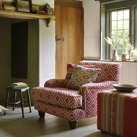 Clarke and Clarke -  Navajo Fabric Collection - A red and white diamond print armchair, a striped cube shaped stool, striped and diamond print cushions, and a black stool