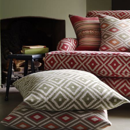 Clarke and Clarke -  Navajo Fabric Collection - A striped cushion with a red, orange, grey and white sofa and three cushions, all featuring two different diamond prints