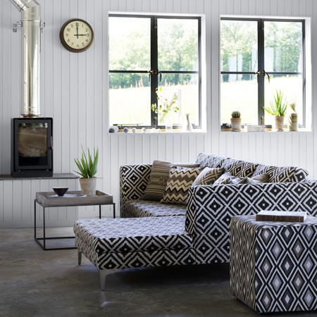 Clarke and Clarke -  Navajo Fabric Collection - Two black, grey and white diamond prints on a corner sofa and cube seat, with matching cushions, a table and a silver tray