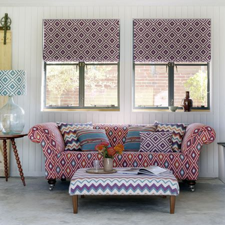 Clarke and Clarke -  Navajo Fabric Collection - Stripes, zigzags and diamond prints making up blinds, cushions, a sofa, a lampshade and a large footstool in various colours