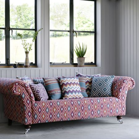 Clarke and Clarke -  Navajo Fabric Collection - A sofa with 8 scatter cushions, all in stripe, zigzag and diamond print fabrics in white, orange, purple and blue shades