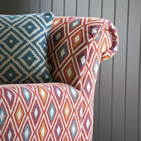 Clarke and Clarke -  Navajo Fabric Collection - Diamond prints covering a cushion in turquoise and off-white, and a sofa in orange, purple, aqua blue, red and cream