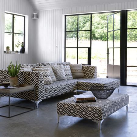 Clarke and Clarke -  Navajo Fabric Collection - Diamond, zigzag and stripe designs covering a large padded footstool, a corner sofa and cushions in black, grey and white