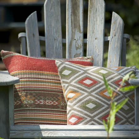 Clarke and Clarke -  Navajo Fabric Collection - Diamonds and tribal style stripes covering 2 cushions in red, orange, khaki, off-white and grey, on a grey wood outdoor seat