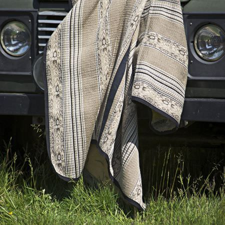Clarke and Clarke -  Navajo Fabric Collection - A throw draped over the front of a car, featuring narrow stripes, patterns and plain sections in various shades of grey