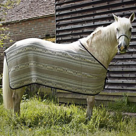 Clarke and Clarke -  Navajo Fabric Collection - A white horse wearing a blanket with plain, striped and patterned strips, made in light shades of grey, with black trim