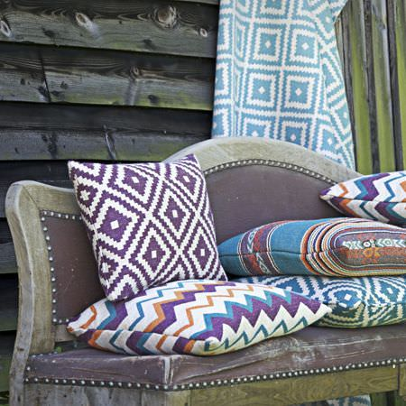 Clarke and Clarke -  Navajo Fabric Collection - A distressed dark purple sofa with a wood frame and striped, zigzag and diamond print cushions in blue, white and purple