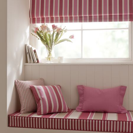 Clarke and Clarke -  New England Fabric Collection - Rosy pink, red and white cushions and roman blinds, in plain and striped patterns in a wood panelled home