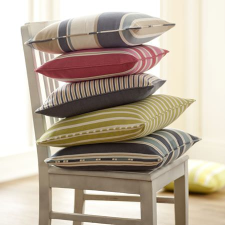 Clarke and Clarke -  New England Fabric Collection - A stack of pink, blue, yellow and white cushions with different width stripes on a white, wooden chair