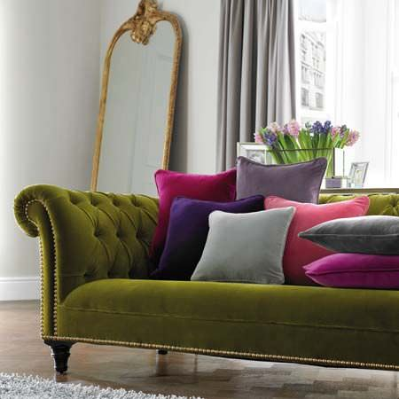 Clarke and Clarke -  Palais Fabric Collection - Cushions in shades of pink, purple and grey on a plain olive green sofa, with a tall mirror, grey curtains and a grey rug