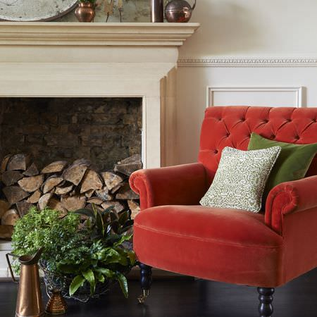Clarke and Clarke -  Palais Fabric Collection - A tomato red coloured armchair with black legs, a plain green cushion, a patterned cushion, a basket, brass jug and a vase