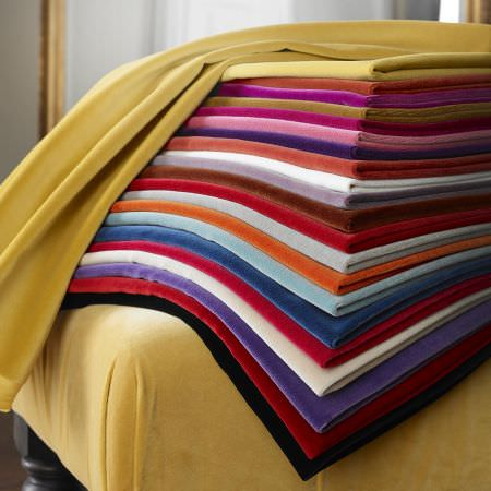 Clarke and Clarke -  Palais Fabric Collection - Folds of various different plain fabrics including pink, orange, red, purple and white colours, on a yellow footstool