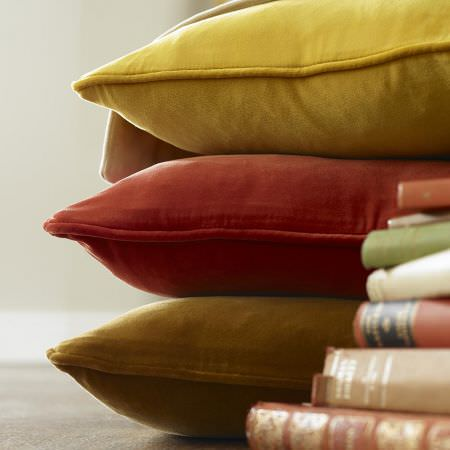Clarke and Clarke -  Palais Fabric Collection - A stack of books beside a plain yellow cushion on top of a plain blood red cushion on top of a plain olive green cushion