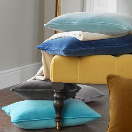 Clarke and Clarke -  Palais Fabric Collection - A yellow footstool with black legs, with a swathe of cream fabric and plain cushions in gold and shades of grey and blue