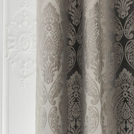 Clarke and Clarke -  Palladio Fabric Collection - Folds of fabric featuring colours fading from white through to dark grey, behind a large, ornate, light grey pattern