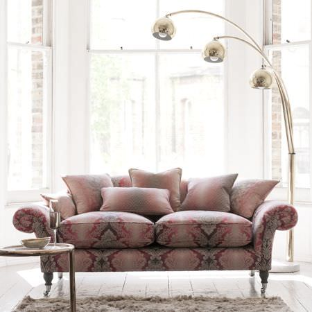Clarke and Clarke -  Palladio Fabric Collection - A large, 3 bulb overhanging floor lamp, with an ornately patterned sofa and cushions fading through red, pink and white