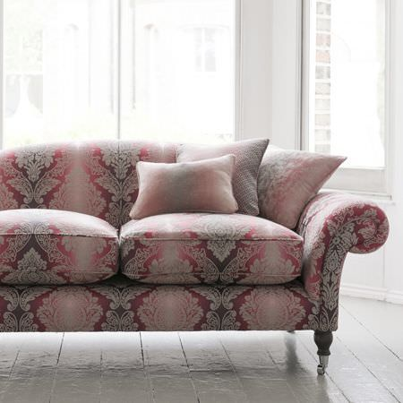 Clarke and Clarke -  Palladio Fabric Collection - A large sofa with 3 scatter cushions, all covered with ornate patterns which fade through red, pink and white colours