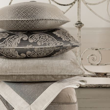 Clarke and Clarke -  Palladio Fabric Collection - A white trimmed grey throw and a plain grey seat cushion with 3 different patterned dark and light grey scatter cushions