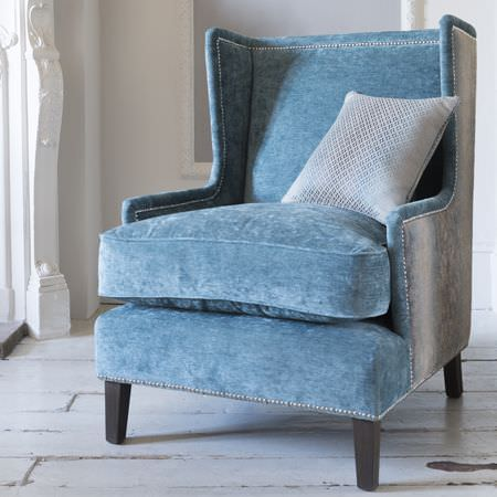 Clarke and Clarke -  Palladio Fabric Collection - A cobalt blue coloured armchair with grey sides, finished with a soft texture, with a subtly patterned pale grey cushion