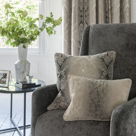 Clarke and Clarke -  Palladio Fabric Collection - A soft, velvety, plain dark grey armchair with 2 ornately patterned cushions and curtains fading through shades of grey