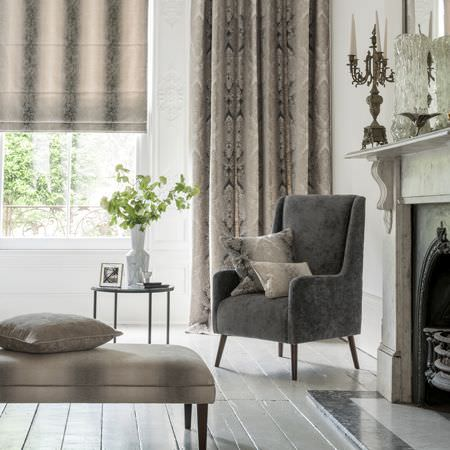 Clarke and Clarke -  Palladio Fabric Collection - A plain grey armchair, with a footstool, blind, cushions and curtains fading through several shades of grey, with a table