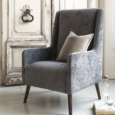 Clarke and Clarke -  Palladio Fabric Collection - A plain grey armchair with a soft texture and wood legs, a square pale grey scatter cushion, books, a bottle and a glass