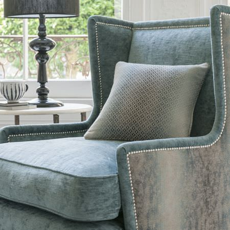 Clarke and Clarke -  Palladio Fabric Collection - Light dusky blue armchair with light grey sides and a soft, sumptuous texture, a patterned cushion and a dark grey lamp