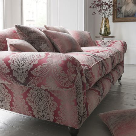 Clarke and Clarke -  Palladio Fabric Collection - A sofa covered with a large, ornate pattern fading through red, pink and white colours, with matching scatter cushions