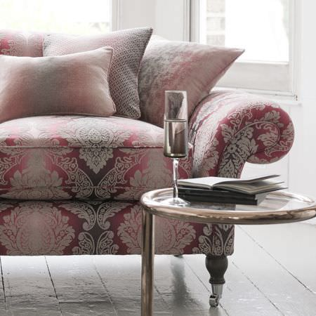 Clarke and Clarke -  Palladio Fabric Collection - A champagne flute on a round pewter coloured table, beside an ornately patterned, red, pink and white sofa and cushions